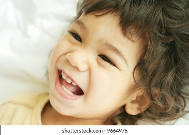 Beautiful toddler boy lying on bed laughing and smiling. Part asian, scandinavian descent.