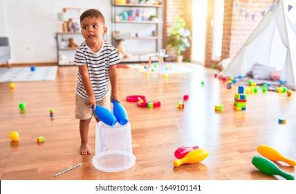 Beautiful toddler boy playing drum using skitlle and plastic basket at kindergarten