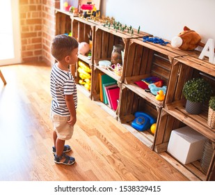 Beautiful toddler boy standing at kindergarten with lots of toys