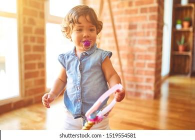 Beautiful toddler child girl wearing blue denim shirt standing on the floor using pacifier