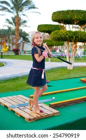 Beautiful toddler european model child girl posing with mini golf equipment on green field outdoor in tropical resort