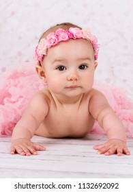 Beautiful toddler with floral headband crawling on the floor wearing tutu skirt