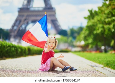 Beautiful toddler girl with French national tricolor flag near the Eiffel tower in Paris, France. 14 July (Bastille day), main French national holiday