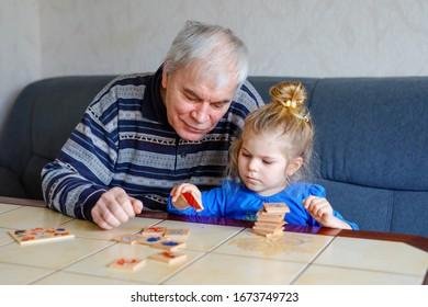 Belle petite fille et grand-père jouant ensemble des images carte de table à la maison. Joli enfant et homme âgé s'amusant ensemble. Famille heureuse à l'intérieur