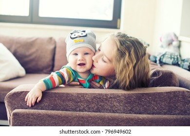 Beautiful toddler girl kissing her little brother at home, laughing and embracing with love and care