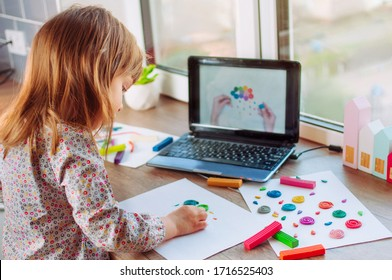 Beautiful toddler girl molding colorful clay cloud with rain watching online learning lesson on the laptop indoor. Distance home learning concept.
