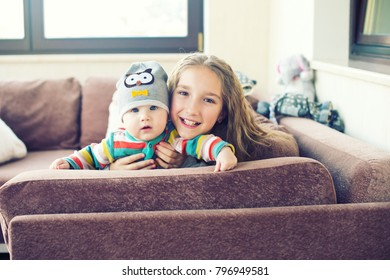 Beautiful toddler girl playing with her little brother at home, laughing and embracing with love and care