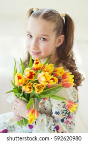 Beautiful toddler girl sitting in the room with fresh tulips, smiling with happy face, waiting for spring and Easter