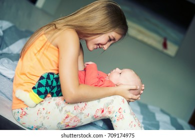 Beautiful toddler girl sitting in room and holding her little newborn baby brother on hands smiling