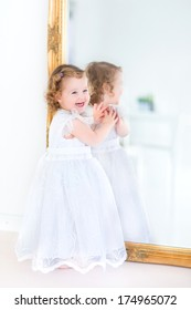 Beautiful toddler girl in a white dress standing next to a big mirror