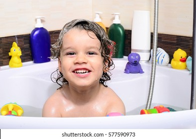 Beautiful toddler taking a bath in a bathtub with bubbles. Cute kid washing his hair with shampoo in the shower and splashing water everywhere