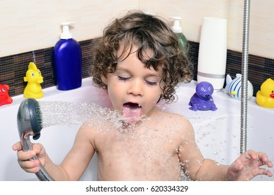 Beautiful toddler taking a bath in a bathtub with bubbles. Cute kid washing his hair with shampoo in the shower and splashing water everywhere. Boy playing with toys in the tub