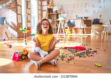Beautiful toddler wearing glasses and unicorn diadem sitting on the floor at kindergarten crazy and mad shouting and yelling with aggressive expression and arms raised. Frustration concept.