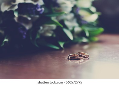 Beautiful toned picture with wedding rings lie on a wooden surface against the background of a bouquet of flowers