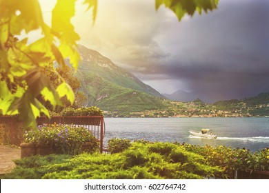 Beautiful toned water scape of coastline of Italian city with focus on mountain on background, leaf on foreground, trees and dramatic cloudy sky before the rain