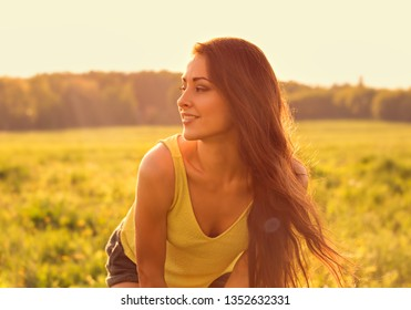 Beautiful toothy natural smiling relaxing woman looking happy with long amazing hair on nature bright sunset summer background. Closeup