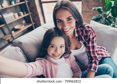 Beautiful with toothy smile mother and her cute daughter are having a video conversation with the father, who is abroad now, they are sitting on a sofa at home