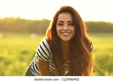 Beautiful toothy smiling young woman looking happy with long amazing bright hair on nature bright sunset summer background. Closeup portrait