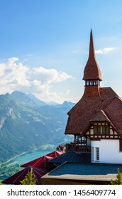 Beautiful top of Harder Kulm in Swiss Interlaken photographed in summer sunset with paragliders flying around. Turquoise Lake Thun in background. Alpine landscape. Travel destination