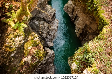 Beautiful top view of a blue mountain river flowing between two high rocks with green plants in Georgia. Martvili canyon. Okatse canyon