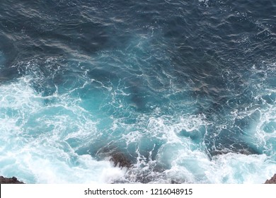 Beautiful top view of powerful waves in the blue and turquoise sea hitting the rock. Nature and lifestyle concept