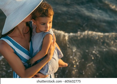 Beautiful top view of young mother kiss daughter at the sea sunset and beach background. Happy family vacation. Travel. Caucasian happy female with baby outside at ocean sunset. Motherhood love care