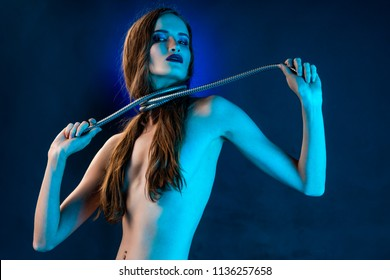 Beautiful topless brunette girl covers her naked breast with her hair and pulls a metal shower spiral hose wrapped around her neck. Conceptual, fashionable, technology and advertising design.