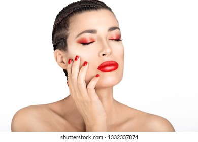 Beautiful topless sensual young woman with red lips and nails and subtle eye makeup touching her hand to her cheek with closed eyes and a serene expression over white in a glamour and beauty concept