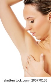 Beautiful and topless woman is touching her armpit. Over white background.