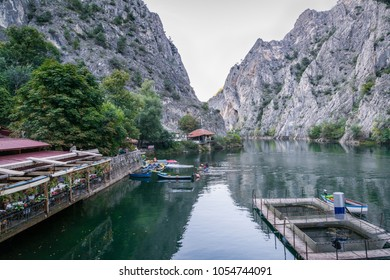 Beautiful tourist attraction Lake Matka in Skopje Macedonia with restaurant and canoes surrounded by mountains.