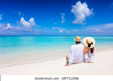 A beautiful tourist couple with hats sits on a tropical beach and enjoys the view to the turquoise ocean during their summer holiday - Shutterstock ID 1897113286