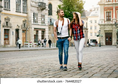Beautiful Tourist Couple In Love Walking On Street Together. Happy Young Man And Smiling Woman Walking Around Old Town Streets, Looking At Architecture. Travel Concept. High Quality Image.