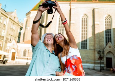 Beautiful tourist couple taking selfie with digital camera, at the city square.