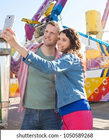Beautiful tourist couple visiting amusement park using smart phone taking selfies pictures, smiling together sunny outdoors. Joyful holiday day out activities, recreation leisure lifestyle technology.