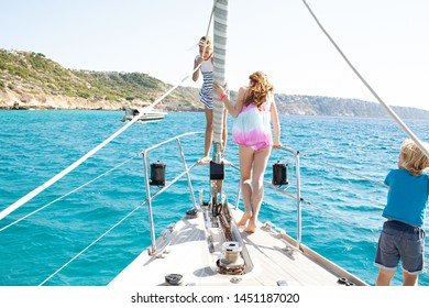 Beautiful tourist family traveling on sunny sailing boat luxury holiday, fun adventure summer activities outdoors. Young people coastal trip on exclusive yacht, aspiration leisure recreation lifestyle