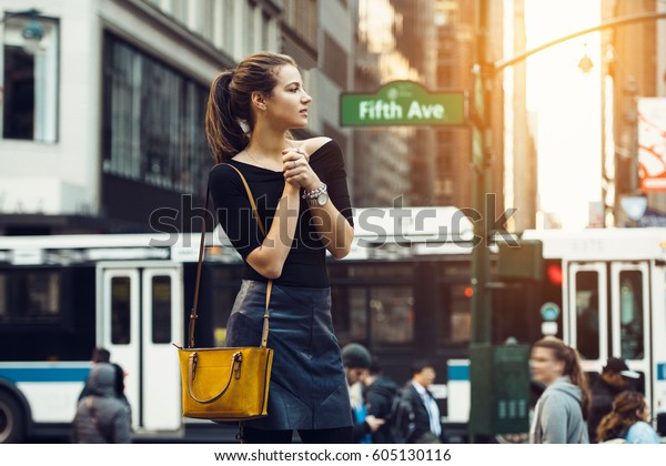 Beautiful tourist girl traveling and enjoing busy city life of New York City. Lifestyle shoot of travel blogger girl on city street.