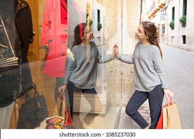 Beautiful tourist teenager in shopping street looking at clothes in store window with manikins and glass reflections, outdoors. Young woman consumer with carrier bags, leisure recreation lifestyle.