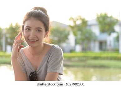 A beautiful tourist woman has playing phone in the evening with sunset time at garden park and river.