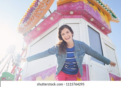 Beautiful tourist woman visiting colorful funfair amusement park, expressive fun energy playful day out activities, solo traveller leisure recreation outdoors. Female enjoying holiday, lifestyle.
