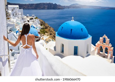 A beautiful tourist woman in a white summer dress looks at the blue domed church of the village of Oia, Santorini, Greece, during her summer holidays