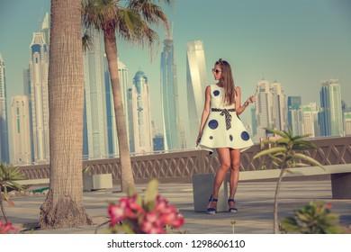 Beautiful tourist woman wolking on Dubai marina.