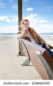 Beautiful tourist young woman sitting on bench in coastal destination, relaxing holiday outdoors. Contemplative female by the sea with sunny blue sky, healthy travel recreation leisure lifestyle.