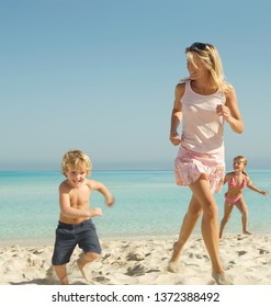 Beautiful tourists family running by the sea on beach summer holiday with blue sky, outdoors. Mother and children on sunny vacation enjoy playing together, travel leisure recreation coastal lifestyle.