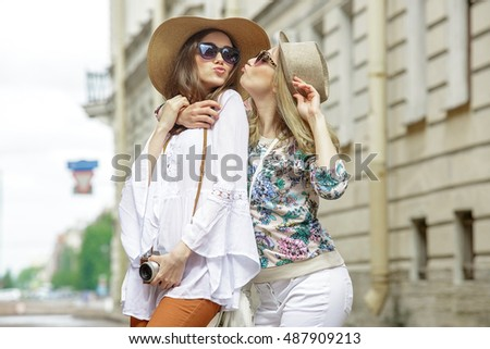 80552193b41c Beautiful tourists on the streets of old European city. Girls wearing hats  and sunglasses.