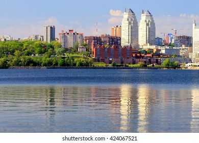 Beautiful towers, buildings and skyscrapers are reflected in the water of the Dnieper River in the early summer morning. Dnepropetrovsk, Dnipropetrovsk, Dnepr city, Dnipro, Ukraine.
