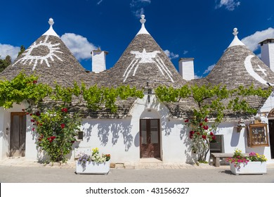 Beautiful town of Alberobello with trulli houses among green plants and flowers, main turistic district, Apulia region, Southern Italy