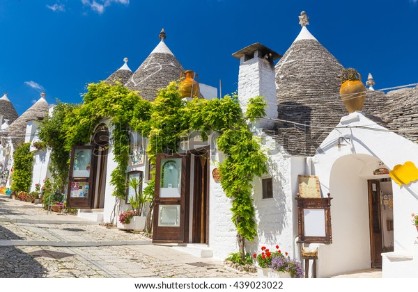Beautiful town of Alberobello with trulli houses among green plants and flowers, main touristic district, Apulia region, Southern Italy