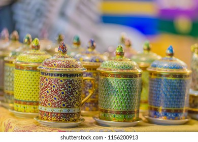 Beautiful traditional Benjarong, Thai five-colored porcelain ceramic cups. Benjarong Porcelain mugs for sale in the flea market, Thailand.