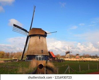 Beautiful traditional Dutch windmill with blue sky background in Alkmaar, Netherlands.