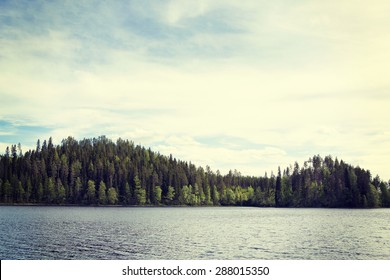 A beautiful and traditional Finnish scenery. A lake with a forest in a sunny day with clouds. Image has a strong vintage effect.